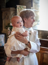 Picture of Revd Wendy Izod with bay in her arms at christening